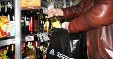 Femeie prinsă cu sticla de alcool în geantă